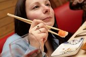 picture of chinese restaurant  - The girl eats sushi in japan restaurant