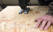 Cutting An Osb Panel With A Jigsaw, Hand On The Panel poster