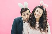 Young Lovers Couple On The Pink Background. With A Bunny Ears On The Head. Having Embraced His Wife, poster