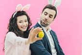 Young Couple On Pink Background. On The Head Is A Bunny Ears. The Wife Holds The Yellow Egg On The E poster