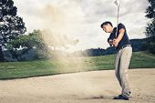 stock photo of trap  - Male golfer in blue shirt and grey pants hitting golf ball out of a sand trap with sand wedge and sand caught in motion - JPG