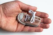 In A Large And Strong Male Hand Is A Small Childrens Shoes. On Shoes Tied With A Bow Bow. A Hand Wit poster
