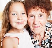 Elderly woman with great-grandchild poster