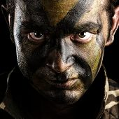 stock photo of special forces  - young soldier face with jungle camouflage paint on black background - JPG