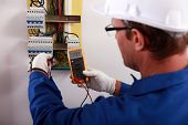stock photo of dungarees  - An electrician checking the energy meter - JPG