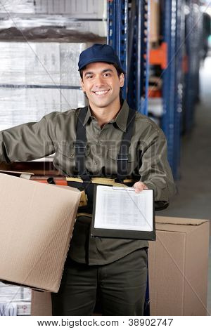 Portrait of young male supervisor with clipboard and cardboard box at warehouse