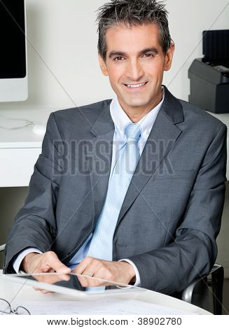 Portrait of businessman with digital tablet sitting at desk in office