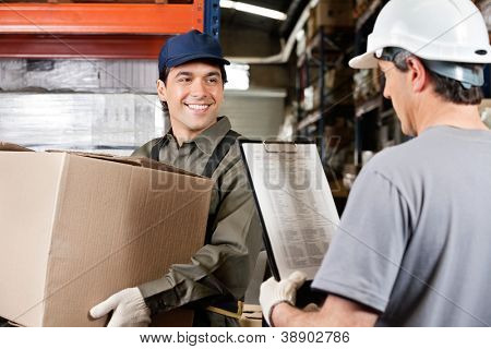 Young warehouse worker with cardboard box looking at male supervisor with clipboard