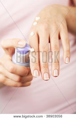 aplicar la crema en las manos de mujer