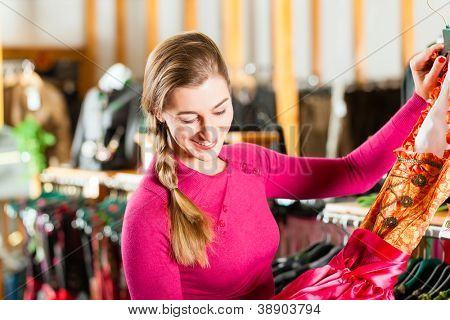 Traditional clothes -young woman is buying Tracht or dirndl in a shop