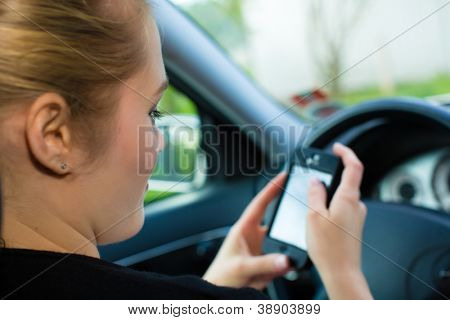 Young woman, in car with mobile phone , checking her text message or her navigation