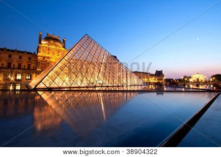 PARIS-APRIL 16: Reflection of Louvre pyramid shines at dusk during the Summer Exhibition April 16, 2010 in Paris. Louvre is the biggest Museum in Paris displayed over 60,000 sq.M. of exhibition space.