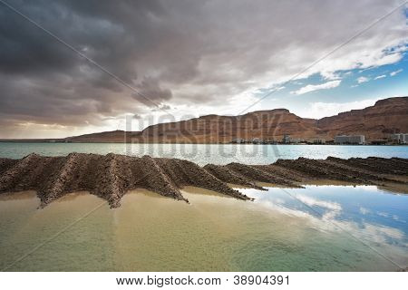 Sunset. Incredible lighting effects on the Dead Sea in Israel. Picturesque sediment mixture of sea salt and mud on the beach