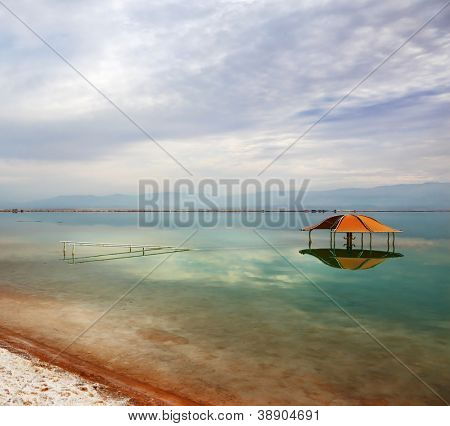 Winter in the Dead Sea. Excellent optical effects and reflections of clouds and sun in the water. The picturesque red gazebo in the water near the shore