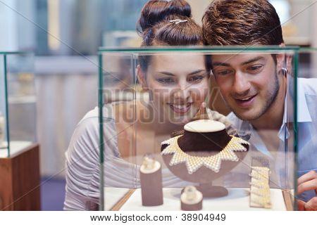 feliz casal romântico apaixonado compra anel de jóias em loja de luxo