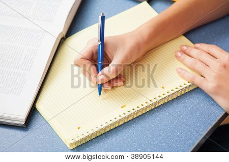 Woman writing in a note pad, closeup photo