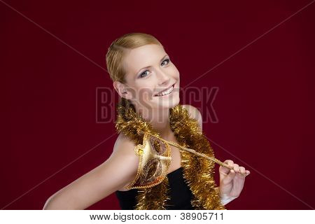Attractive woman with masquerade mask and tinsel, isolated on purple