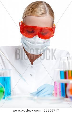 Young female lab assistant does some tests, chemistry concept, isolated on white