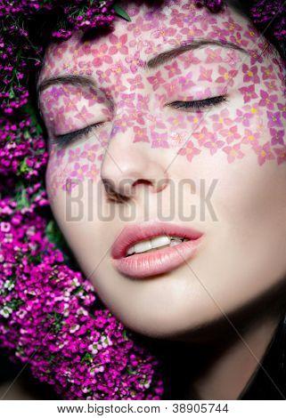 Close-up retrato do modelo florido maquiagem moda e grinalda com olhos fechada
