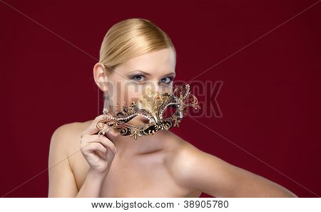 Woman with patterned masquerade mask, isolated on purple
