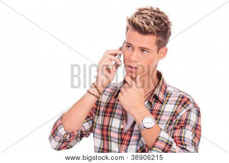 closeup picture of an attractive young man posing pensive on the phone