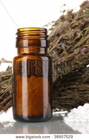 bottle of medicines with herbs on white background. concept of homeopathy
