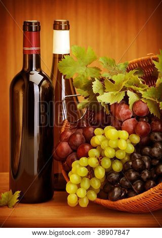 Photo of grape wine still life, two bottle of vine and basket with different kind of grapes on wooden table, alcohol beverage, fresh juicy fruits, winery restaurant, harvest season, luxury concept