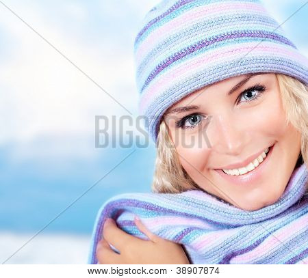 Photo of cute blond girl wearing blue warm beanie and scarf, closeup portrait of nice woman dressed stylish wool hat isolated on winter background, wintertime fashion, New Year holidays concept