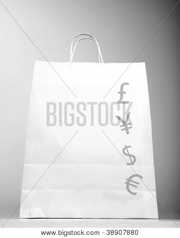 Photo of white shopping bag with money sign isolated on gray background, successful business, foreign money symbol, paper present bag, saving money concept, commercial store, new purchase