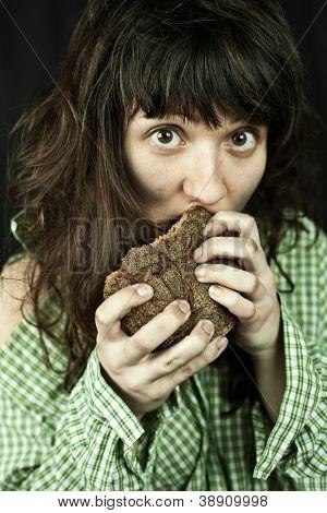 portrait of a poor beggar woman eating bread in her hands
