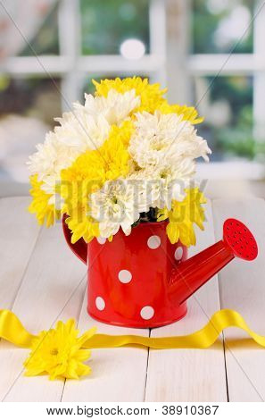 Red watering can of peas with flowers on white wooden  table on window background
