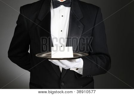 A butler wearing a tuxedo holding a note card on a silver tray in front of his torso. Man is unrecognizable over a light to dark gray background.