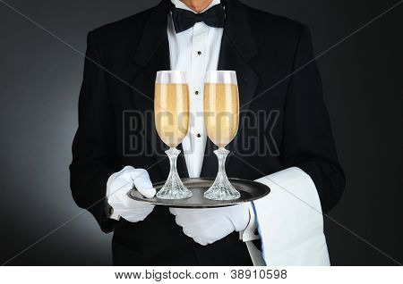 Closeup of a Sommelier holding two champagne glasses on a tray in front of his torso. Horizontal format on a light to dark gray background.