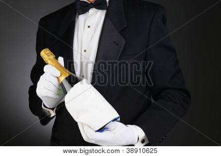Closeup of a Sommelier holding a Champagne bottle in front of his torso. Man is unrecognizable. Horizontal format on a light to dark gray background.