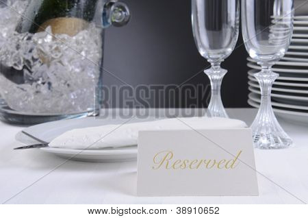 Closeup of a Reserved sign on a restaurant table that is set for an elegant occasion. Shallow depth of field.