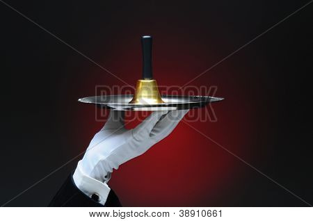 Closeup of a white gloved hand holding a service bell on a silver tray. Horizontal format on a light to dark red background.