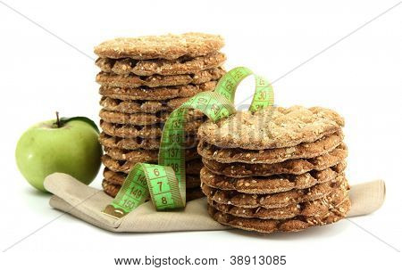 tasty crispbread, apple and measuring tape, isolated on white