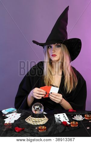 Witch - fortuneteller on color background