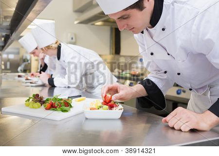 Chef preparing a fruit salad in a busy kitchen