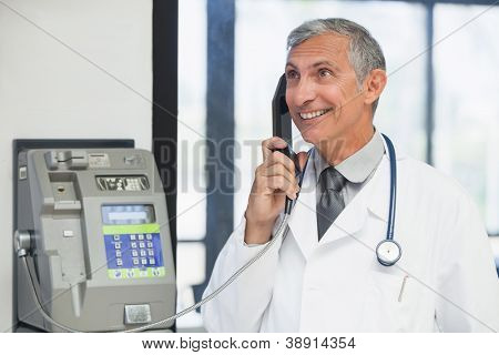 Doctor on a payphone and smiling in hospital corridor