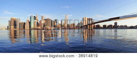 Brooklyn Bridge mit niedrigeren Manhattan Skyline Panorama am Morgen mit Wolke und Fluss-Reflexion