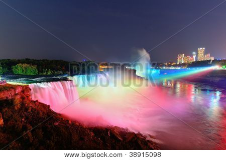 Niagara Falls lit at night by colorful lights