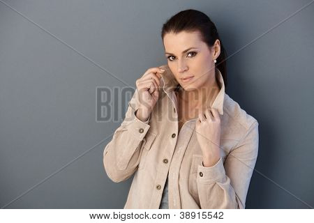 Mid-adult woman posing in spring jacket, holding collar, looking at camera determined.