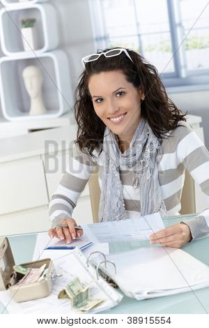 Smiling woman calculating finances at home, checking bills, counting money.