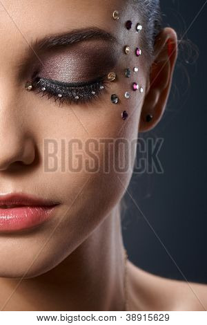 Partial facial portrait of beautiful woman wearing luxury makeup with strasses, closed eyes.