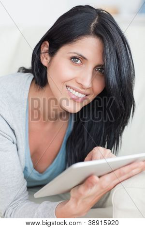 Close up of a smiling woman playing with a tablet in a living room