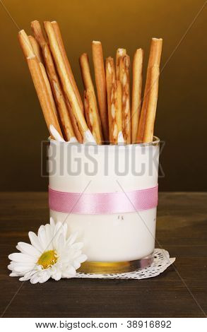 Tasty crispy sticks in glass with sour cream on wooden table on yellow background