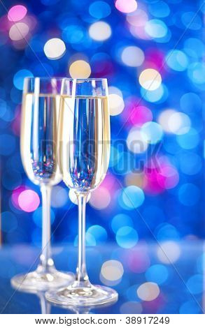 Two glasses of champagne with lights in the background. very shallow depth of field, focus on near glass.