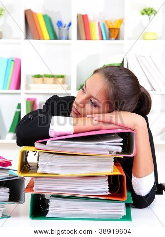 Tired business woman with documents in her workplace