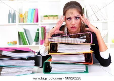 müde geschäftsfrau mit Dokumenten in ihrem Arbeitsplatz